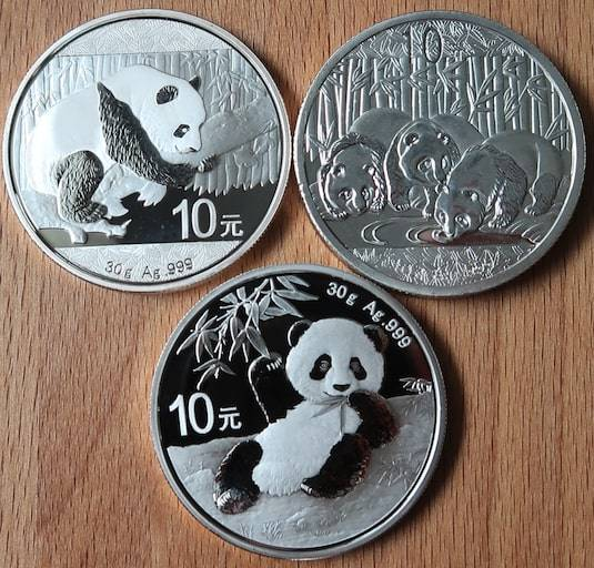 An Image of the several authentic Chinese Silver Pandas along with a counterfeit Chinese Silver Panda